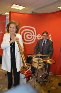 La embajadora peruana María Teresa Merino de Hart, Cónsul del Perú en Nueva York, ensaya con un saxo mientras que el Agregado Comercial del Perú en Nueva York, Conrado Falco lo hace con una batería, durante el reciente anuncio de la actividad artística.
