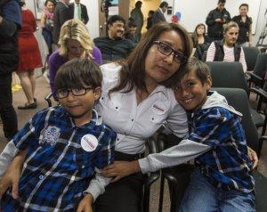 Isabel Medina, de 41 años, se abraza a sus hijos, Rayan (izqda), de seis años, y Jimmy Ortiz (dcha), de ocho, durante el anuncio del presidente de EEUU, Barack Obama, de la nueva reforma migratoria, el 20 de noviembre de 2014 (AFP | Ringo Chiu)